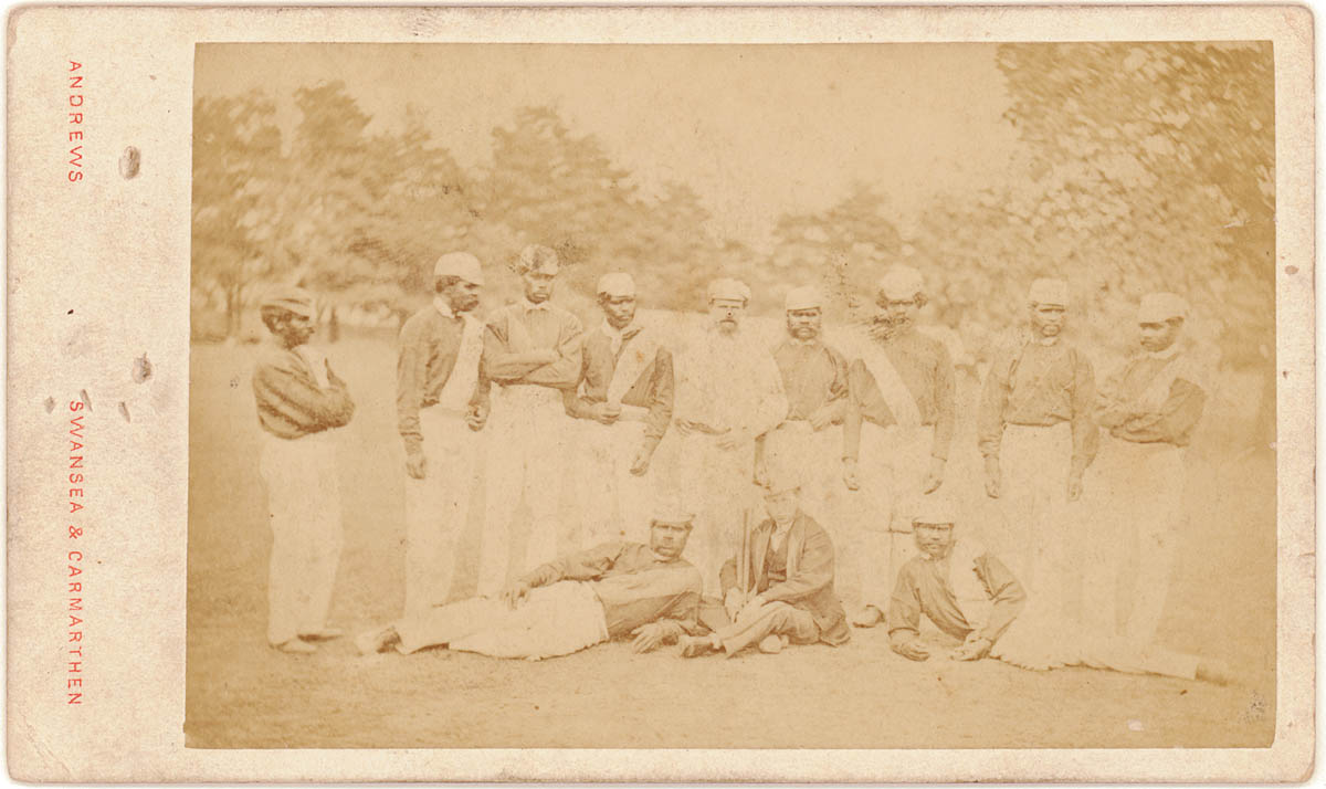 Indigenous Australian cricket players standing and sitting on grass in uniform of the day