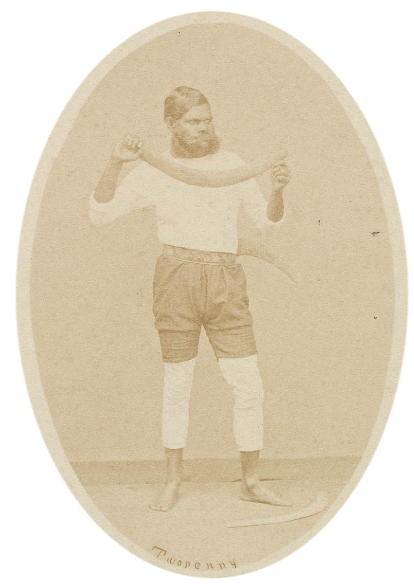 Old portrait of an Indigenous Australian standing with boomerang
