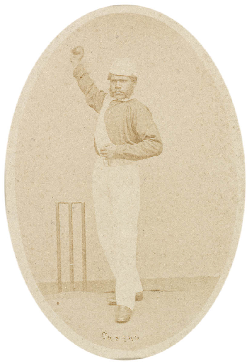 Old portrait of an Indigenous Australian in cricket uniform of the day standing in front of the stumps and holding a cricket ball in the air