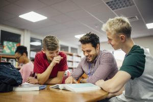 The benefits of volunteering - older male mentor with two students
