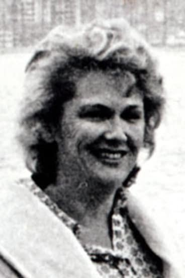 black and white photo woman smiling in checkered shirt with white coat