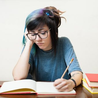 student with blue hair writing in book