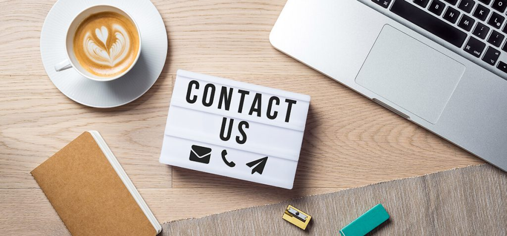 Top down image of a desk with Contact us sign