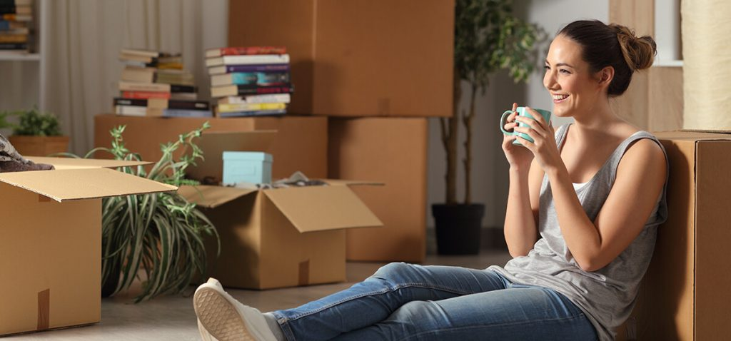 Woman leaning on a box taking a break from moving house.