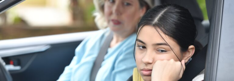 Woman and teenage girl sit in car. Teenage girl annoyed.