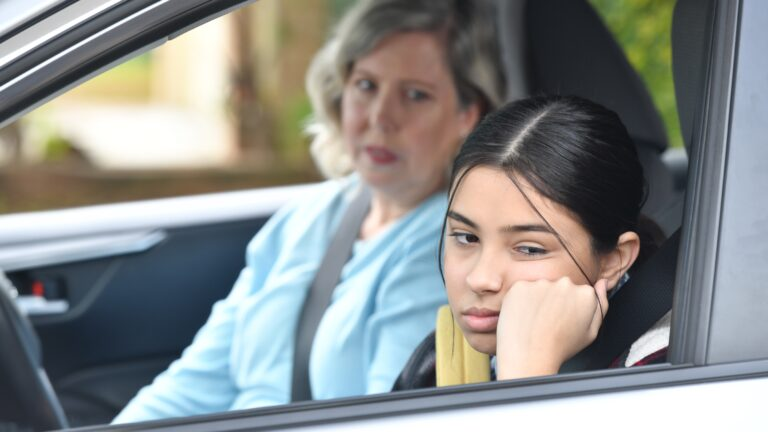 Woman and teenage girl sit in car. Teenage girl annoyed.