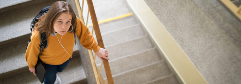 female student walking down a set of stairs