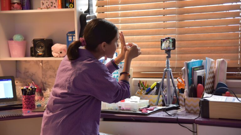Teenage girl sits at desk and holds up jewellery to a camera.