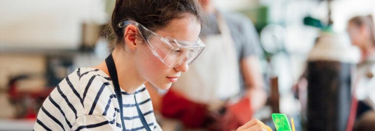 Girl wearing safety glasses doing soldering