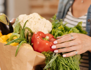 Woman holding a bag full of veggies