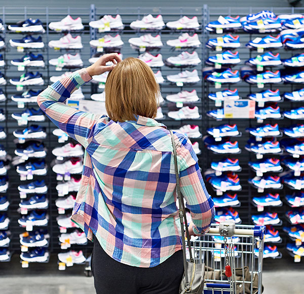 Woman looking at a display full of running shoes