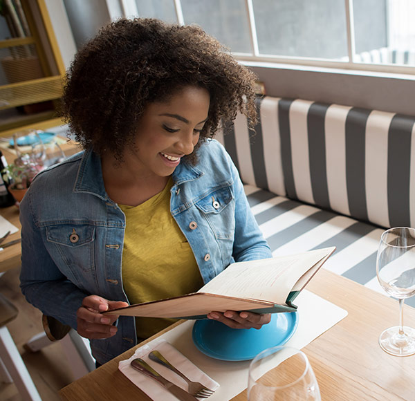 Woman reading a book while sitting at the dining table