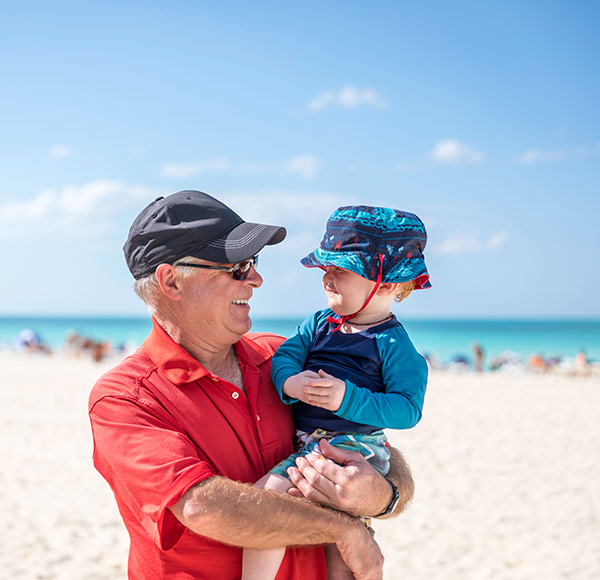 Grandad at the beach holding a kid in his arms