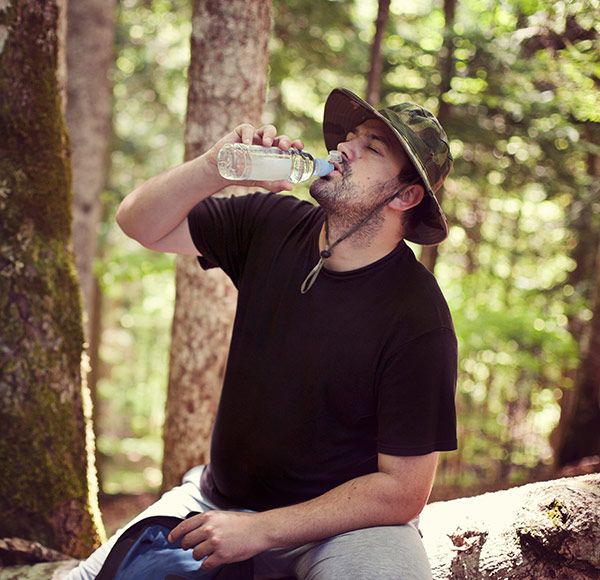 Man drinking water while sitting in the bush