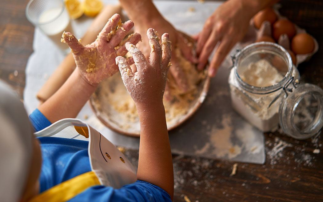 Kids hands preparing and cooking food with parent