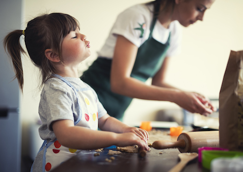 Cute little girl baking at home with mom