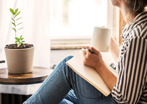 Sitting with coffee mug and pencil pad