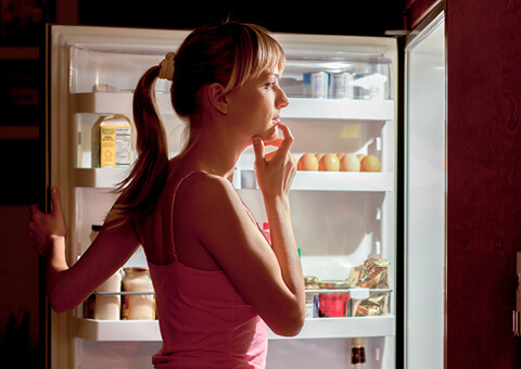 Woman looking at food in the fridge