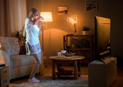 Woman dancing in front of TV