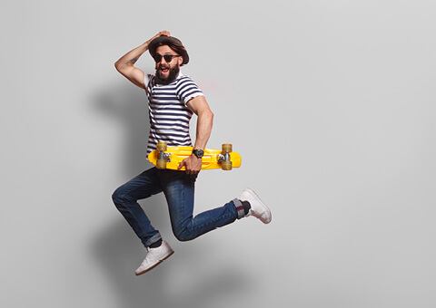 Man jumping on the spot holding skateboard and hat