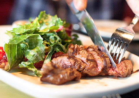 Cutting cooked meat on a plate