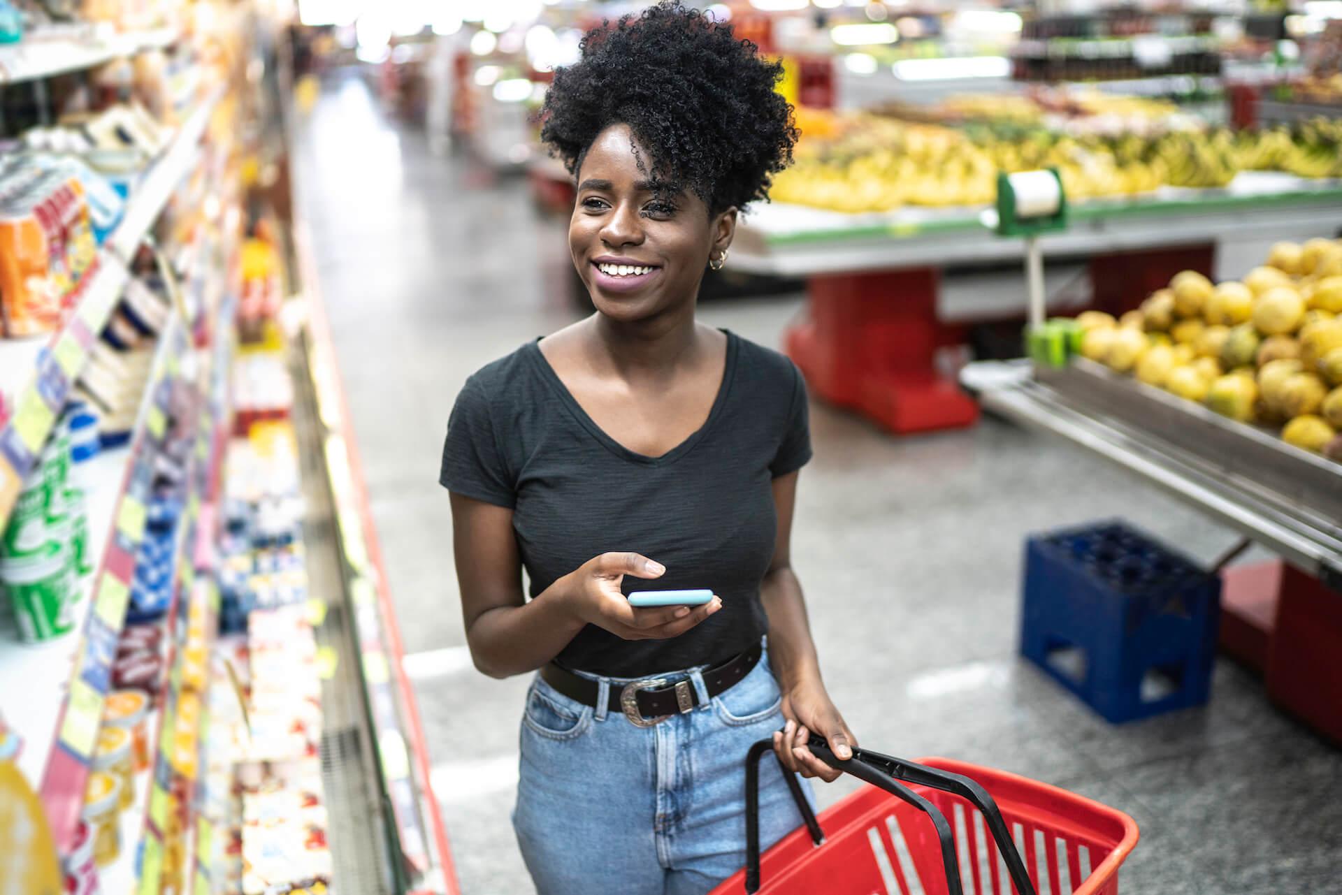 Woman going through shopping list in shopping aisle