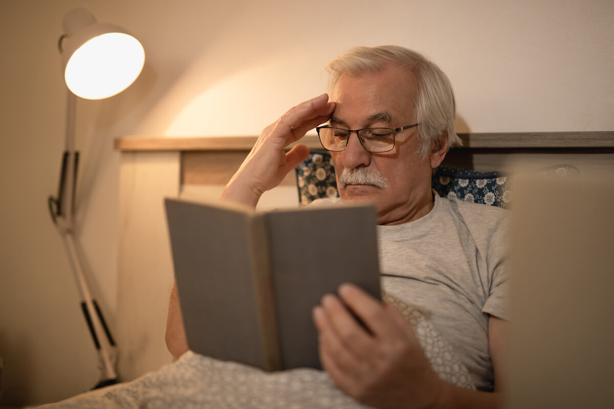 Man reading a book in bed with side table lamp on