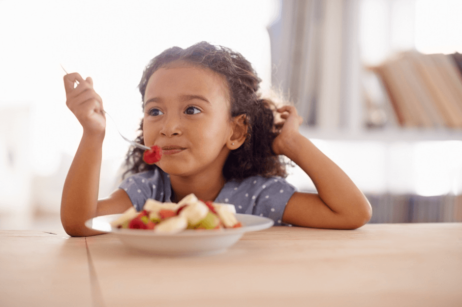 Young girl eating a bowl of fruit