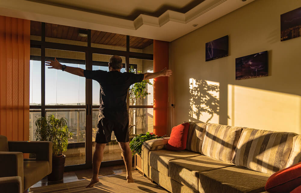 Man stretching arms in front of window