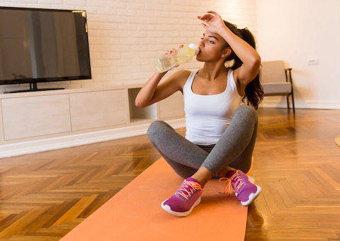 Woman drinking water on yoga mat