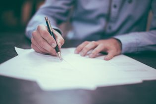 Tips for negotiating a property deal - a man signing a paper
