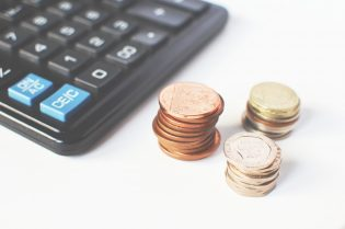 A calculator and pennies to represent how to save for a home loan