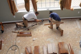 save money on a renovation - two men fixing skirting board