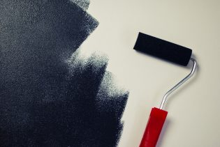 A paint brush on a wall helps to renovate
