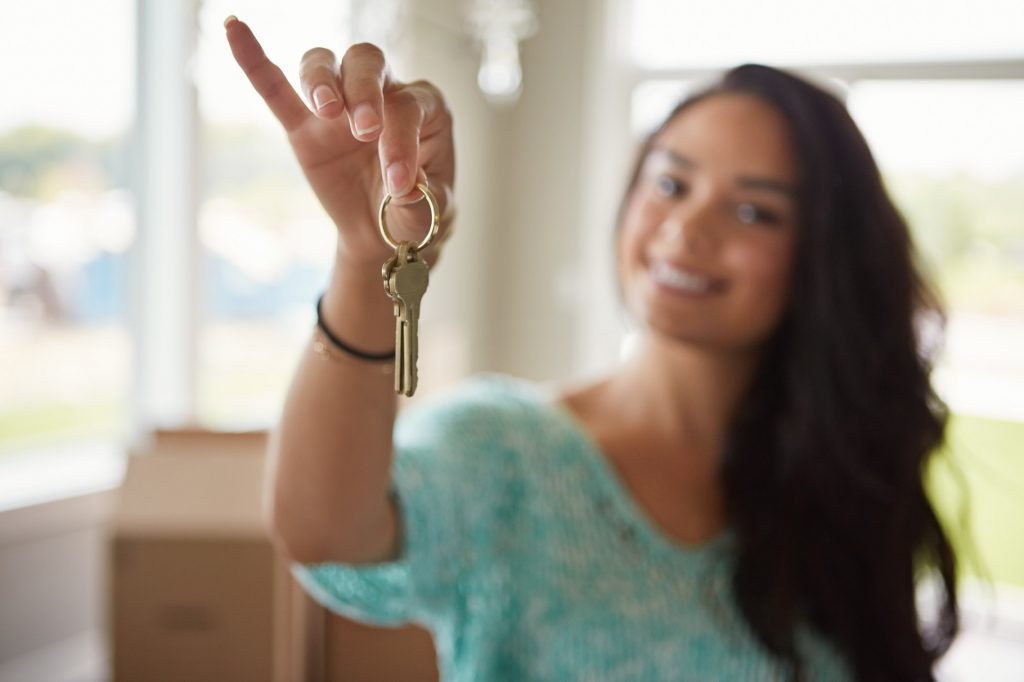 Shot of a woman moving into her new home when renting for the first time