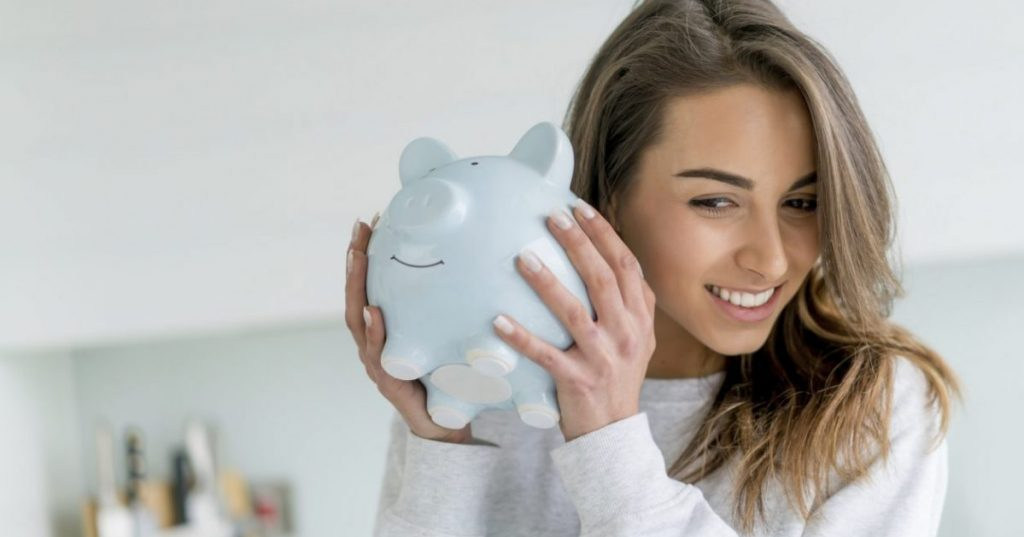Woman holding a piggy bank and saving for a deposit