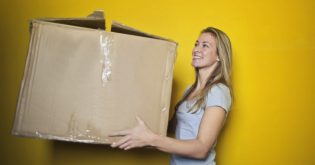 A woman holds a box as she is downsizing a home
