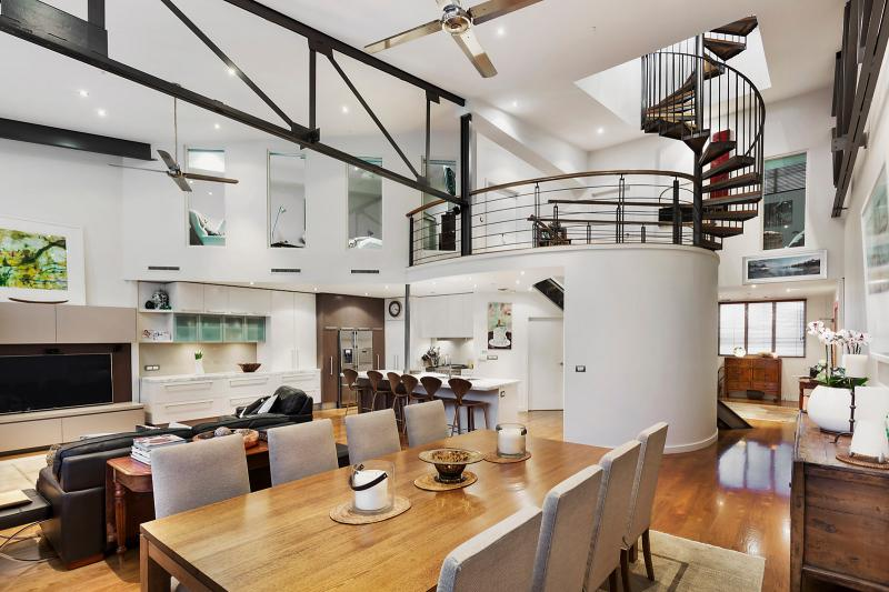 An industrial-style living area with spiral staircase.