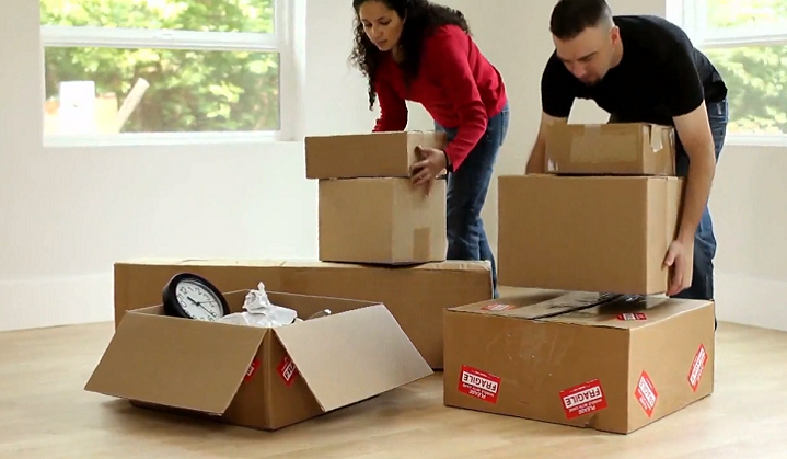 Couple packs up their possessions in boxes