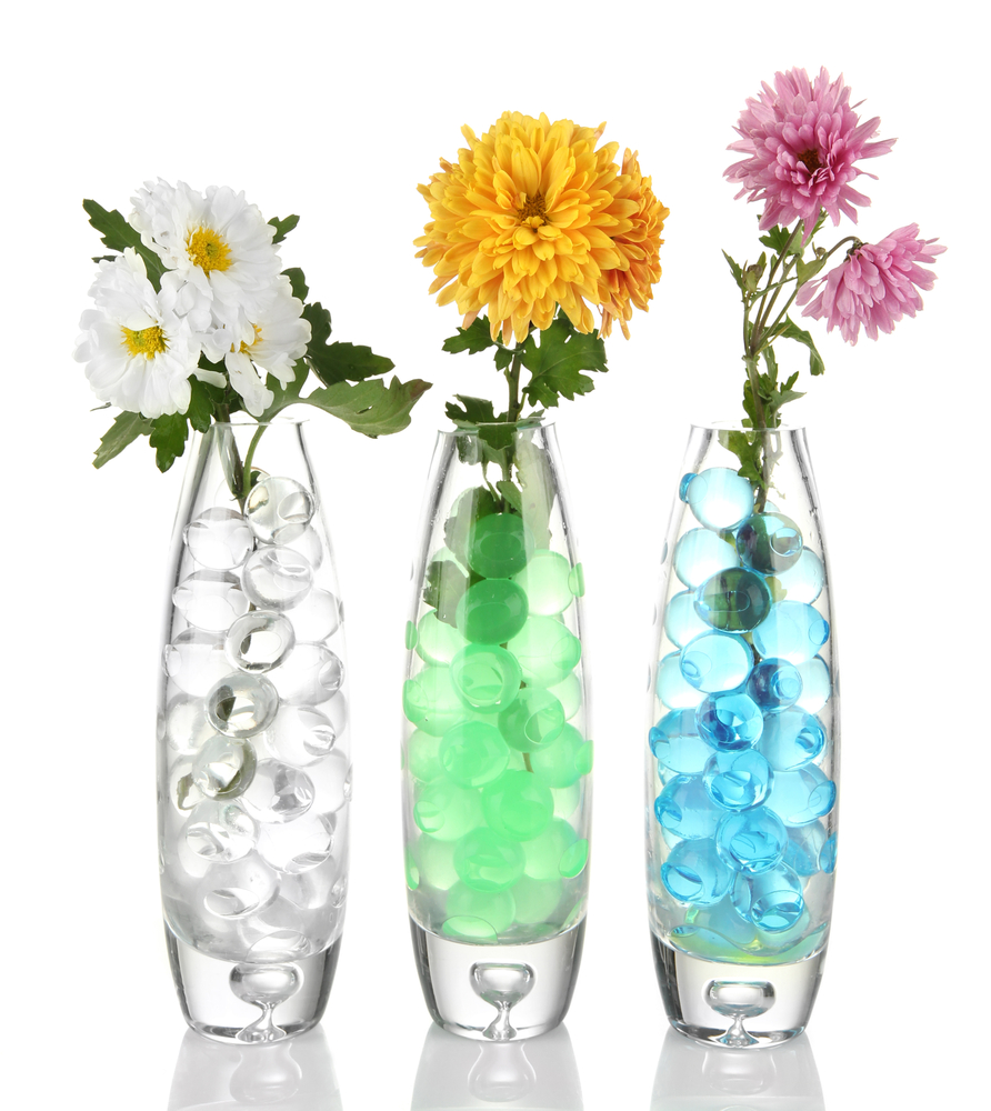 Coloured waterbeads in vases with flowers