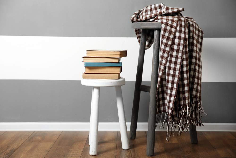A stool being used as a table with books and clothes on it.