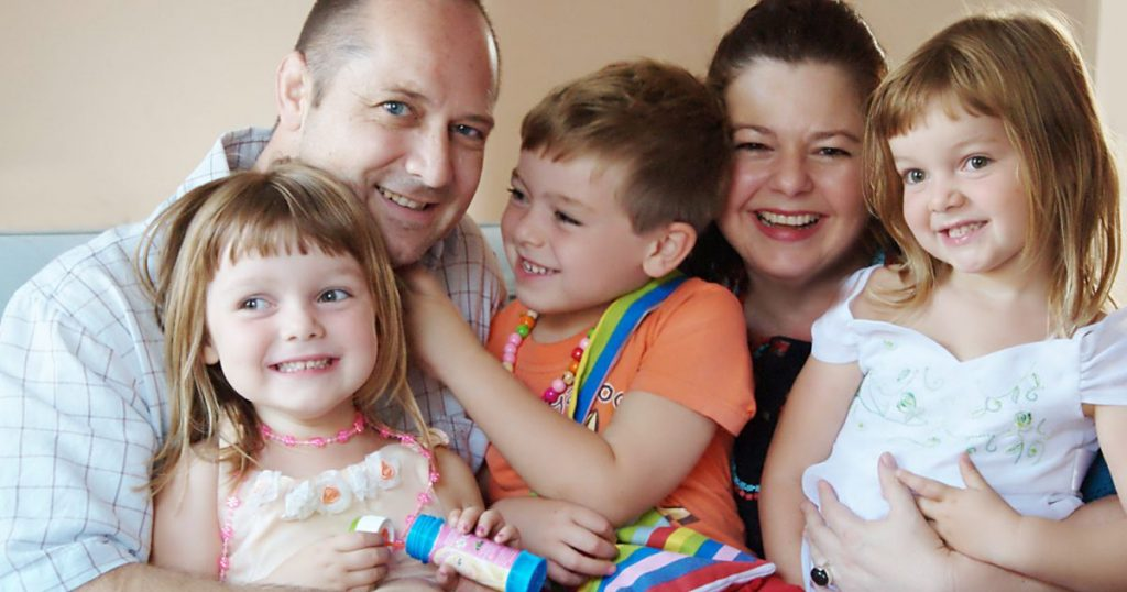 A family enjoy apartment living and smile into the camera