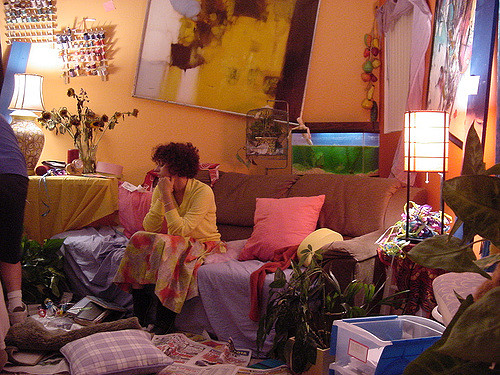 A woman sits in a messy apartment room