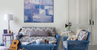 A living room with blue furniture design and artwork