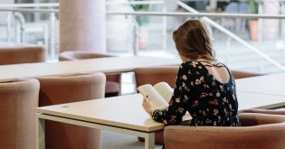 A female student reads a book in a library