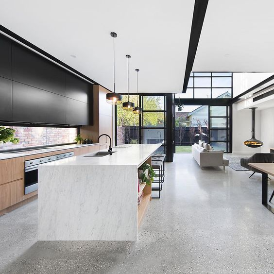 A modern kitchen with dark cupboards and a concrete floor.