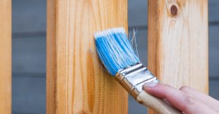 A paintbrush dipped in blue paint runs down a timber panel when renovating for profit
