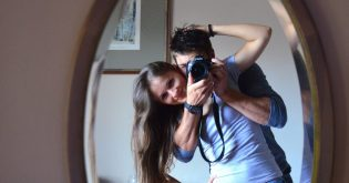 A young couple buy their first home and look into the mirror with a camera