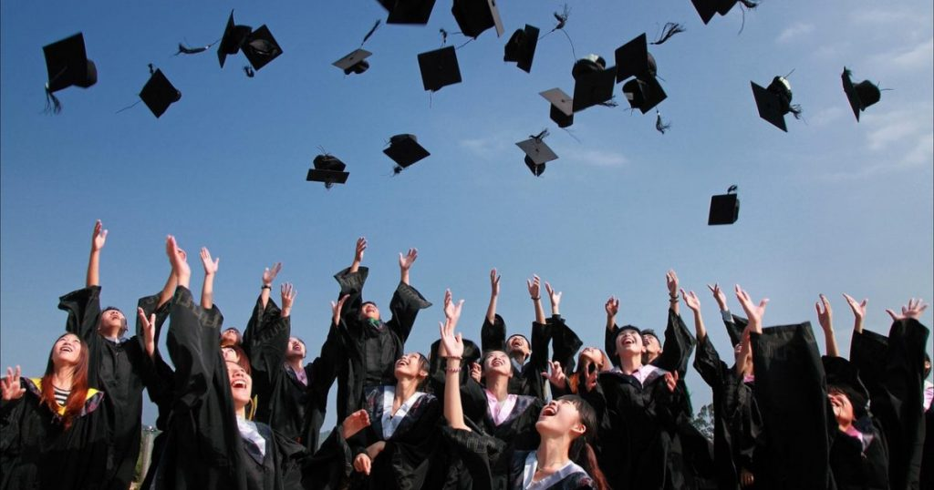 A group of graduates throw their hats into the sky