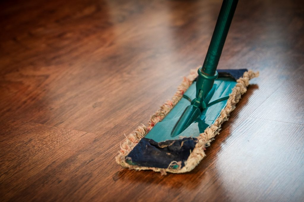 A cloth broom cleans the wooden floorboards.